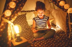 有片剂个人计算机的愉快的儿童女孩在家笑在帐篷的黑暗的 库存照片