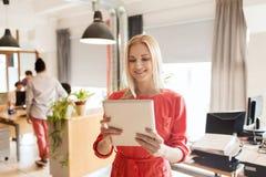 有片剂个人计算机的愉快的创造性的女性办公室工作者 免版税库存图片
