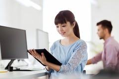 有片剂个人计算机的愉快的创造性的女性办公室工作者 免版税库存照片