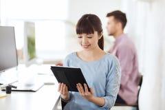 有片剂个人计算机的愉快的创造性的女性办公室工作者 库存图片