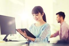 有片剂个人计算机的愉快的创造性的女性办公室工作者 免版税图库摄影