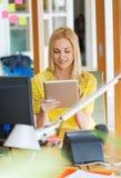 有片剂个人计算机的愉快的创造性的妇女在办公室 免版税图库摄影