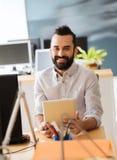 有片剂个人计算机的愉快的创造性的男性办公室工作者 图库摄影