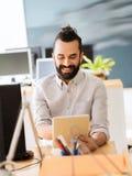 有片剂个人计算机的愉快的创造性的男性办公室工作者 免版税库存照片