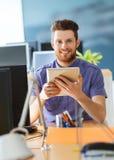 有片剂个人计算机的愉快的创造性的男性办公室工作者 库存照片