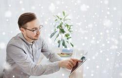 有片剂个人计算机的愉快的创造性的男性办公室工作者 免版税库存图片