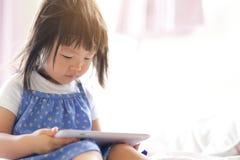 有片剂个人计算机的愉快的女孩 免版税库存图片