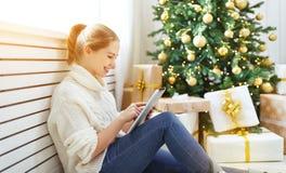 有片剂个人计算机的愉快的妇女在圣诞树附近的早晨 免版税库存图片
