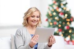 有片剂个人计算机的愉快的妇女在圣诞节 库存图片