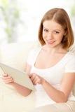 有片剂个人计算机的愉快的妇女在家 免版税库存照片