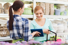 有片剂个人计算机的愉快的妇女在花店 免版税库存照片