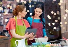 有片剂个人计算机的愉快的妇女烹调在厨房里的 免版税图库摄影