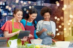 有片剂个人计算机的愉快的妇女烹调在厨房里的 库存照片
