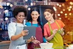 有片剂个人计算机的愉快的妇女烹调在厨房里的 免版税库存照片
