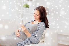 有片剂个人计算机的愉快的孕妇在家 库存图片