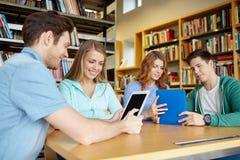 有片剂个人计算机的愉快的学生在图书馆里 免版税图库摄影