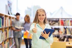 有片剂个人计算机的愉快的学生女孩在图书馆里 免版税库存照片