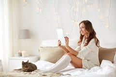 有片剂个人计算机的愉快的少妇在床上在家 免版税库存照片