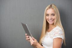 有片剂个人计算机的愉快的美丽的妇女 免版税库存照片