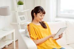 有片剂个人计算机的愉快的年轻亚裔妇女在家 免版税图库摄影