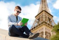 有片剂个人计算机的愉快的年轻人在埃佛尔铁塔 免版税库存图片