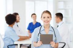 有片剂个人计算机的愉快的医生在诊所的队 免版税库存照片