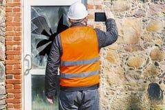 有片剂个人计算机的房屋检查员在残破的窗口附近 库存照片