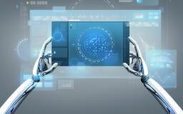 有片剂个人计算机的机器人手在灰色背景 免版税库存图片