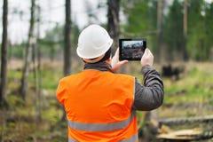有片剂个人计算机的森林官员 免版税库存照片