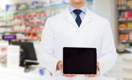 有片剂个人计算机的男性医生在药房 免版税库存照片