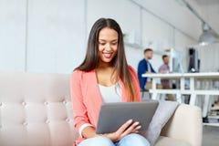 有片剂个人计算机的美国妇女在办公室 免版税库存照片