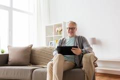 有片剂个人计算机的老人在家坐沙发 库存照片
