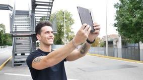 有片剂个人计算机的英俊的年轻人在城市 免版税库存照片