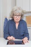 有片剂个人计算机的退休的夫人 图库摄影