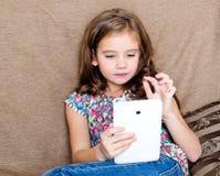 有片剂个人计算机的逗人喜爱的小女孩在沙发在家 库存照片
