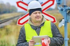 有片剂个人计算机的铁路工程师在警报信号附近 免版税库存图片