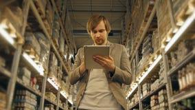 有片剂个人计算机的经理检查物品的在超级市场仓库 股票录像