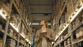 有片剂个人计算机的经理检查物品的在超级市场仓库 图库摄影