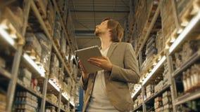 有片剂个人计算机的经理检查物品的在超级市场仓库 库存照片