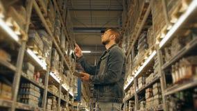 有片剂个人计算机的经理检查物品的在超级市场仓库 库存图片