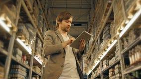 有片剂个人计算机的经理检查物品的在超级市场仓库 免版税库存图片