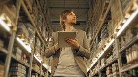有片剂个人计算机的经理检查物品的在超级市场仓库 免版税库存照片