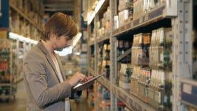 有片剂个人计算机的经理检查物品的在超级市场仓库 免版税图库摄影