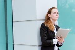 有片剂个人计算机的年轻红头发人女实业家 免版税图库摄影