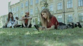 有片剂个人计算机的Thougthful学生学习在草坪的 股票录像