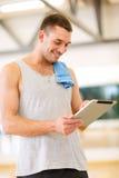 有片剂个人计算机计算机和毛巾的年轻人在健身房 免版税库存图片