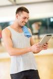 有片剂个人计算机计算机和毛巾的年轻人在健身房 图库摄影