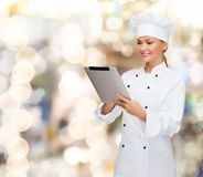 有片剂个人计算机计算机的微笑的女性厨师 图库摄影