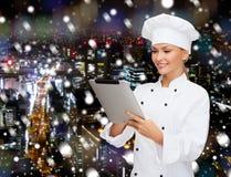 有片剂个人计算机计算机的微笑的女性厨师 免版税库存照片