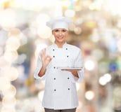 有片剂个人计算机计算机的微笑的女性厨师 库存图片